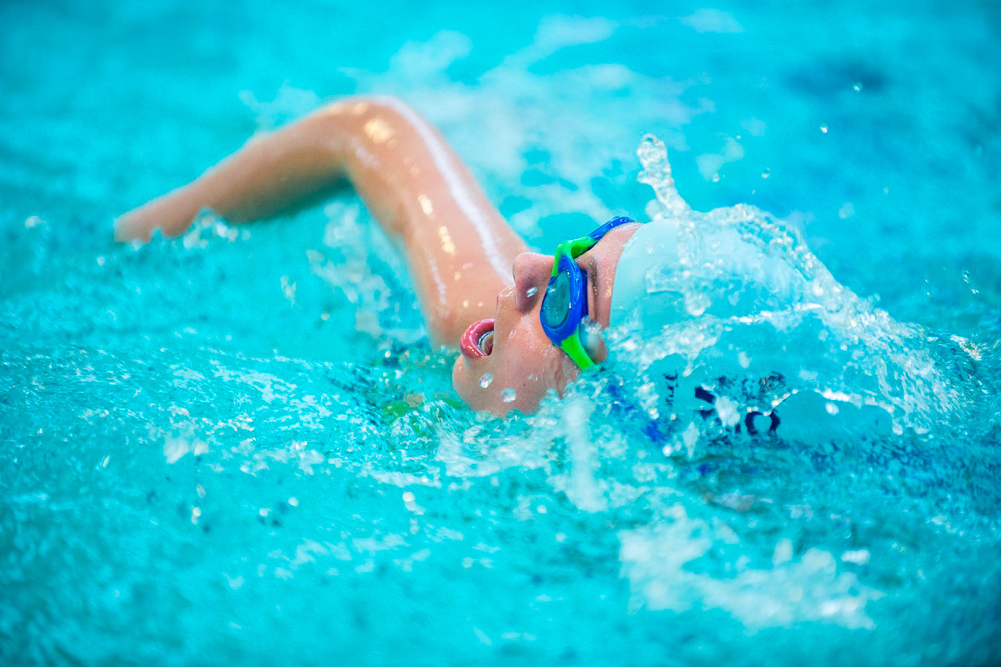 Young Child Swimming In A Swimming Pool
